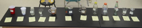 The twelve containers are labeled with sticky notes, while students' initial assessment of  thermal ranking is written on the paper pieces in front of the containers.