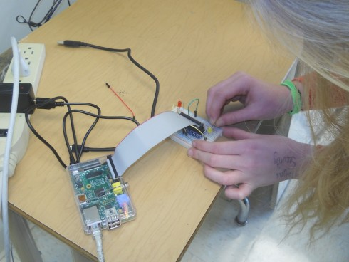 Student wires the breadboard attached to a Raspberry Pi.