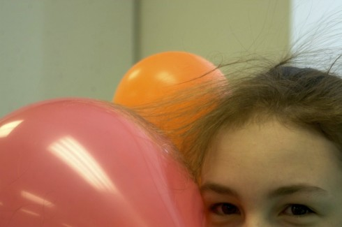 Hair attracted to a balloon by static electrical forces.