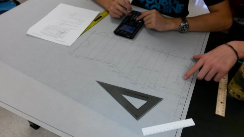 Students drawing trapezoids to fit the outline of the guitar, and calculating their areas.