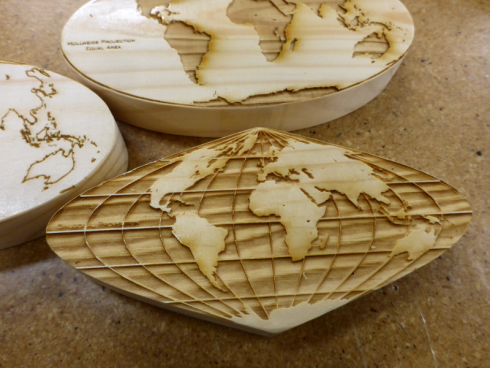 Laser-etched map projections on wood.